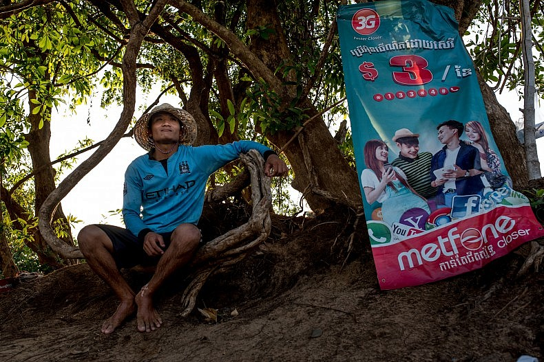 A Bunong man sits next to a cell phone company advertisement. Photo by Luc Forsyth.