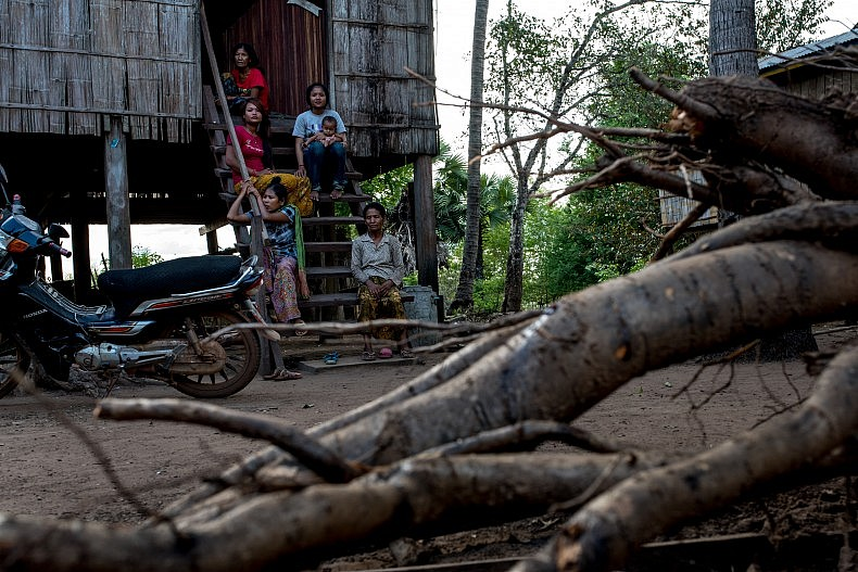 A Bunong family sit in front of their house in the village of Kbal Romeas, northeastern Cambodia. Photo by Luc Forsyth.