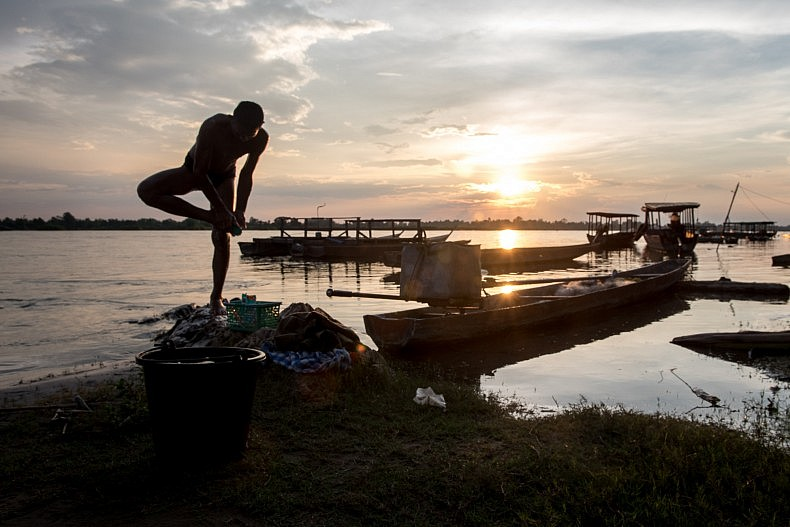 A man washes his feet along the banks of the  Mekong river in the town of Nakasang. Photo by Luc Forsyth.