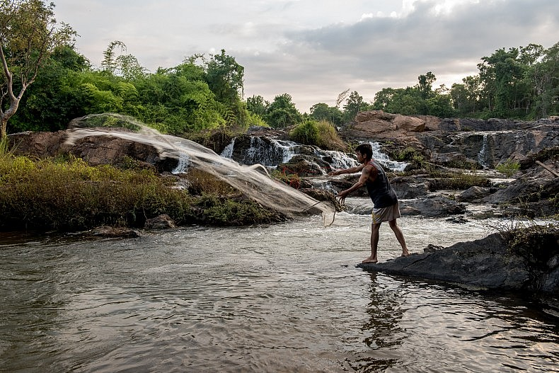 A man casts his fishing net into a pool of water above the Khone Phapheng waterfalls. Photo by Luc Forsyth.