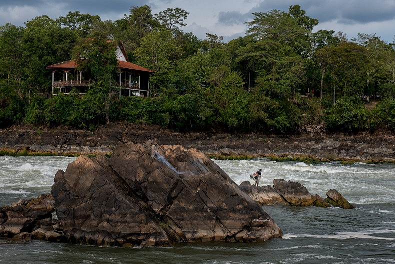 A fisherman casts his net into the turbulent water below the  Khone Phapheng waterfalls. Photo by Luc Forsyth.