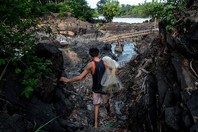 A fisherman walks through a rock field above the Khone Phapheng waterfalls. The rocks are exposed only in the dry season and will be under water when the monsoon rains fall and the Mekong rises to its full size.  Photo by Luc Forsyth.