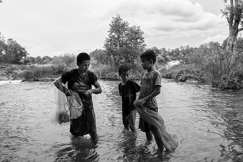 A fisherman and his sons in the Mekong in Laos. Photo by Gareth Bright.