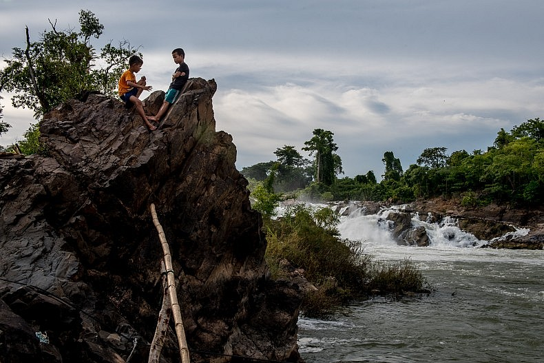 The young sons of a fisherman sit on the banks of the Mekong below the Khone Phapheng waterfalls, waiting for their father to return from his afternoon fishing. Photo by Luc Forsyth.
