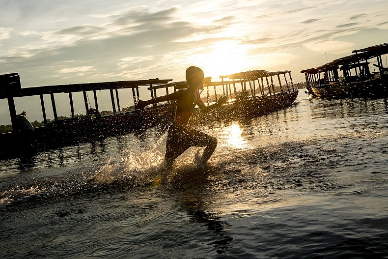 A young boy runs along the bank of the Mekong river near the town of Nakasang. Photo by Luc Forsyth.