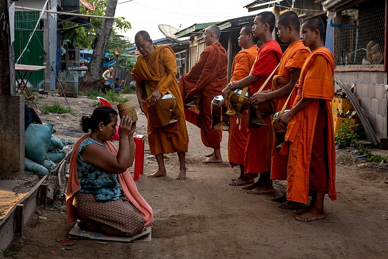 Buddhist monks collect alms from the residents of Nakasang in the early morning.  Photo by Luc Forsyth.