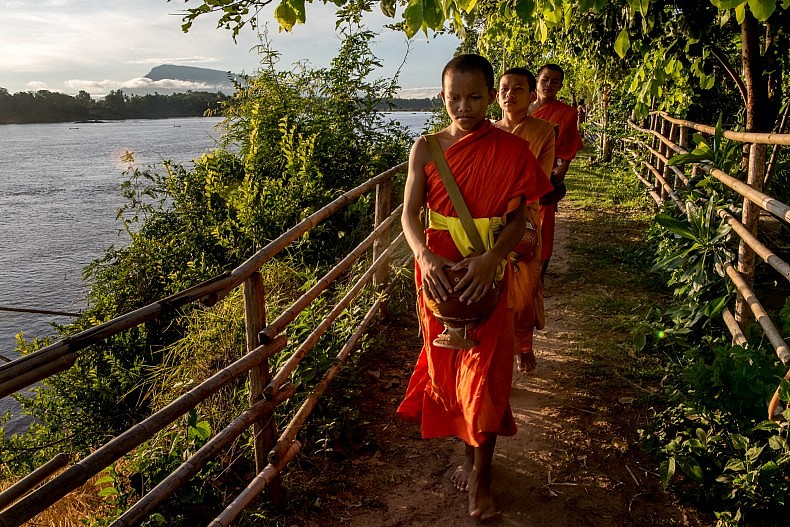 Monks make their morning round to collect alms from the villagers on the island of Don Kho. Photo by Luc Forsyth.