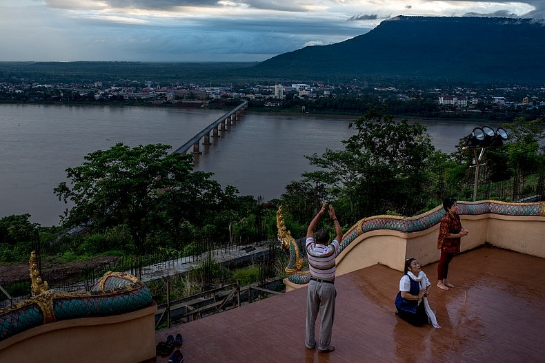 People pray to a large statue of Buddha overlooking the Mekong river in the city of Pakse. Photo by Luc Forsyth.