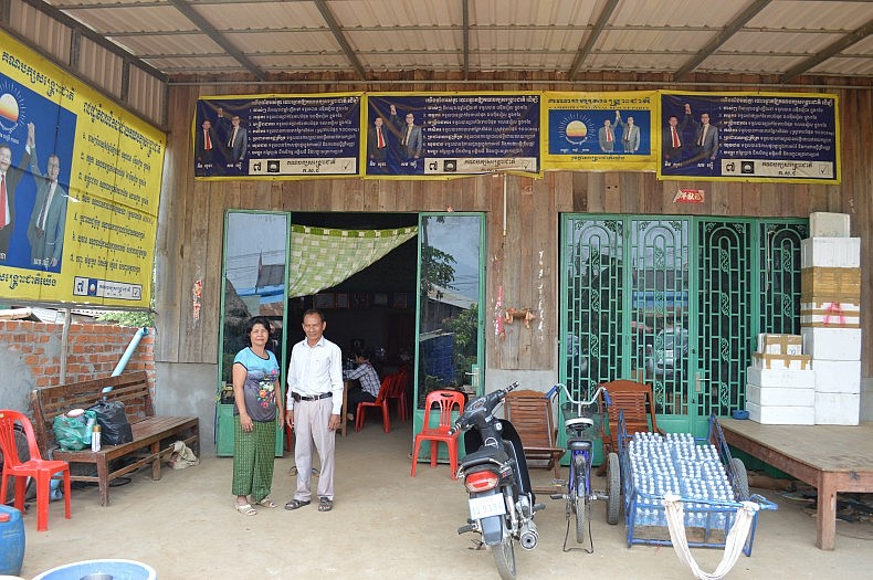 Ven Ra and her husband Kinh Ponh in front of the party headquarters of the opposition CNRP in Pailin. Photo Credit: Anya Palm