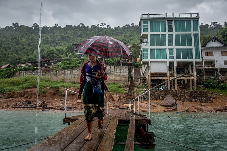 A woman walks towards a floating restaurant on the Nam Ngum dam's reservoir.  Photo by Luc Forsyth.