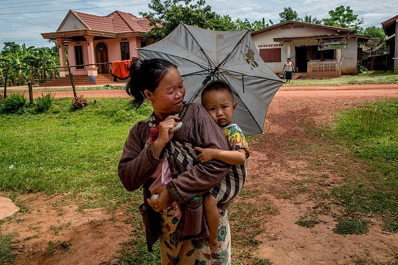 A mother protects her yougn son from the afternoon sun in the village of Baan Thaxan. Photo by Luc Forsyth.