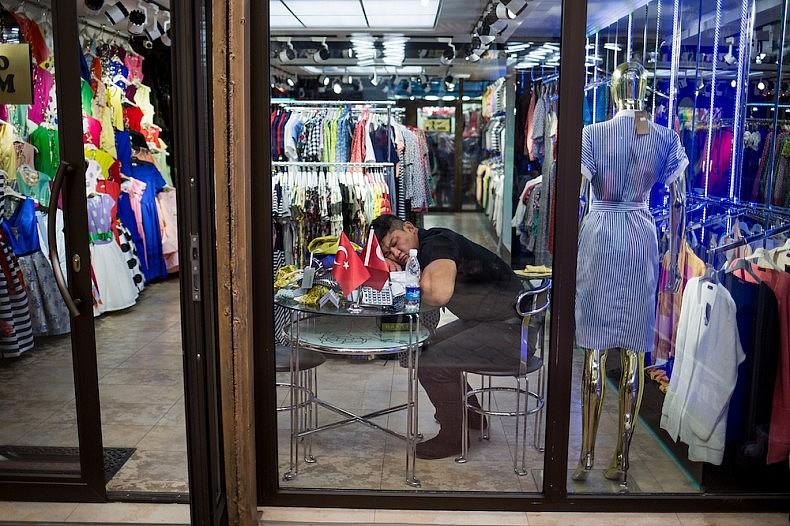 With no customers, a trader naps inside his container-shop  Source: Elyor Nematov
