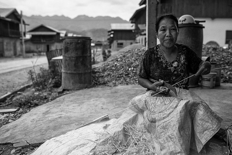 Chan Souk, 62, makes traditional Laos brooms in front of her home in the Samaky Sai relocation camp. She says finding the money to buy food has become a constant problem since being forced to leave her village for the camp.  Photo by Gareth Bright.