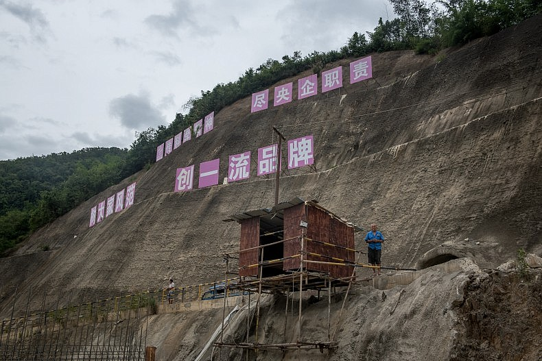 A Chinese security guard watches over the top of the Nam Kong 2 dam, which is still under construction. Photo by Luc Forsyth.