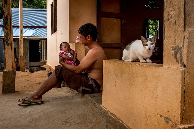 A man with his newborn baby in the village of Khoc Kham. Photo by Luc Forsyth.