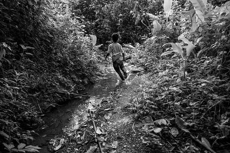 A boy runs down a path outside the village of Khoc Kham. Photo by Gareth Bright.