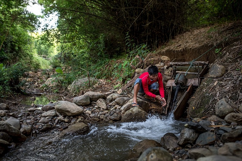 A man checks on his families water turbine in the village of Khoc Kham. Photo by Luc Forsyth.