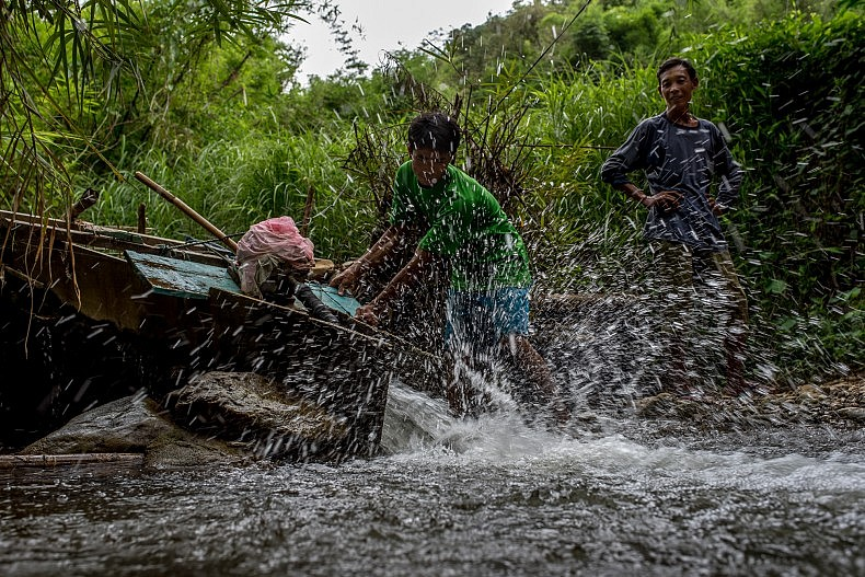 A man turns on his water turbine as evening approaches in the village of Khoc Kham. Photo by Luc Forsyth.