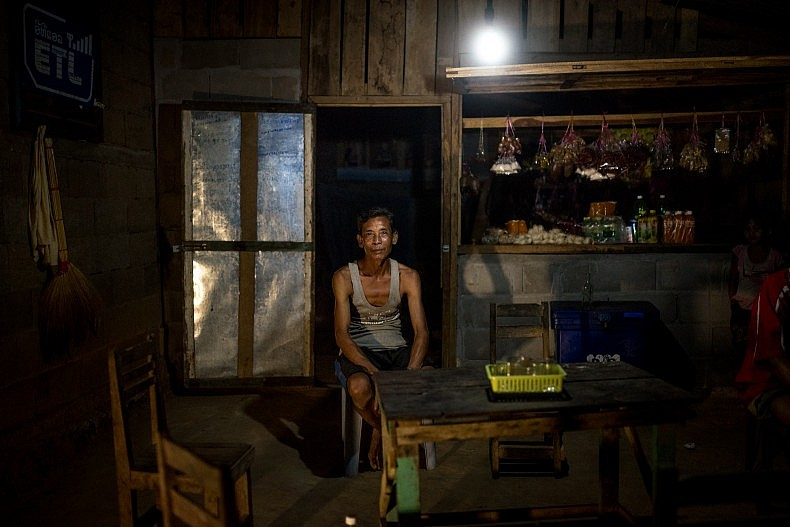 Xieng Pai, 54, is a shopkeeper in the village of Khoc Kham. He powers the light in his shop using a portable water turbine. Photo by Luc Forsyth.