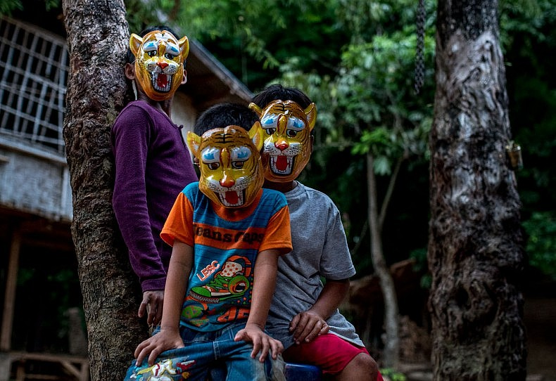 Children wear plastic masks in the village of Khoc Kham. With the introduction of affordable outboard motors, the villagers, who have no road access to the outside world, can trade with nearby villages. Photo by Luc Forsyth.