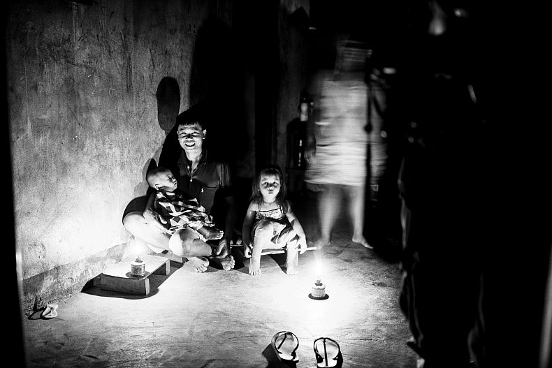 Villagers in Khoc Kham gather around a light powered by their own electricity generation system. Photo by Gareth Bright.