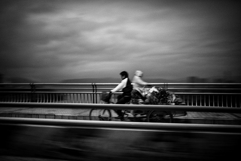 Two locals cross each, early morning, on a  bridge spanning the Lancang (Mekong) in Xishuangbanna, Yunan, China. Photo by Gareth Bright.
