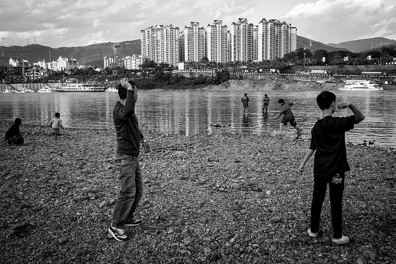 Tourists and locals gather to skips stones and play along the Lancang (Mekong) river in Xishuangbanna, Yunan, China. Photo by Gareth Bright.