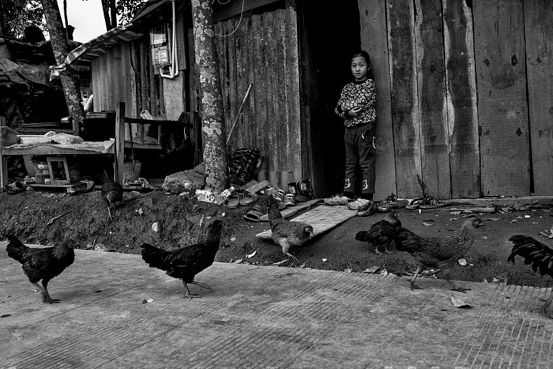 A young girl stands outside her family home in Manhenuan village. Photo by Gareth Bright.