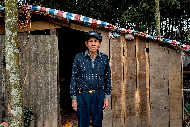 Yan Ying, 52, stands in front of his home in Manhenuan. Photo by Luc Forsyth.