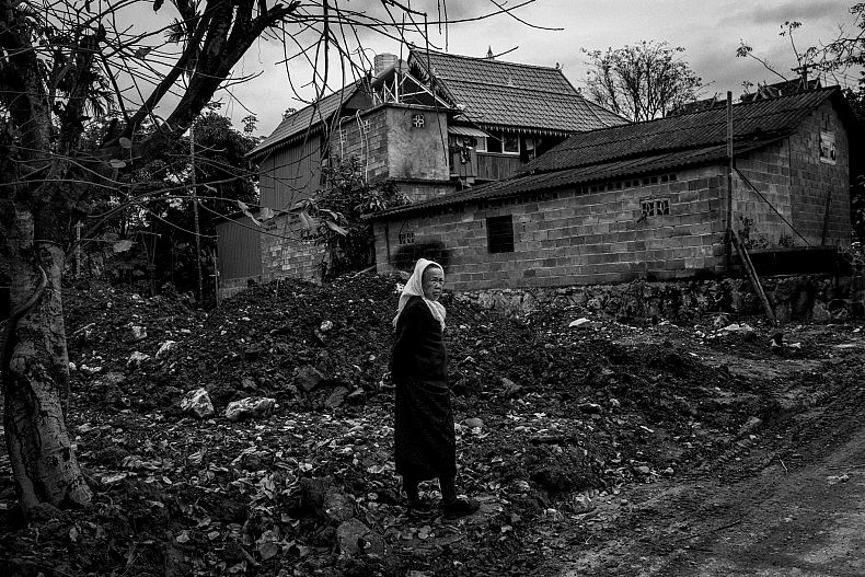A woman stands in a demolished plot of land in Manhenuan village. Photo by Gareth Bright.