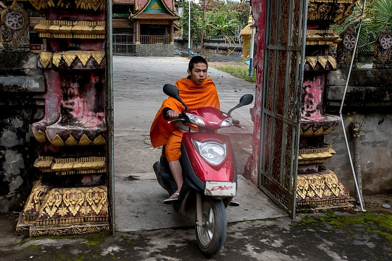 A monk drives a scooter in  the Olive Dam Dai cultural village in Xishuangbanna, China. Photo by Luc Forsyth.