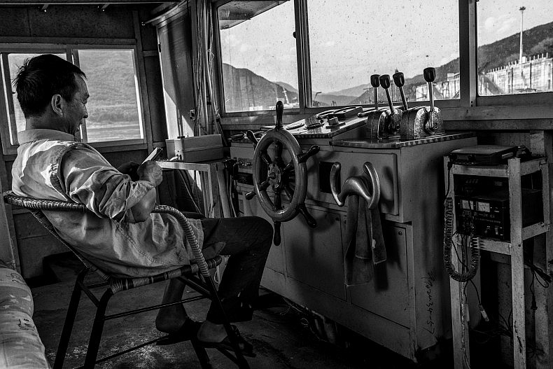 The captain of a sand dredging vessel mans the cockpit in the early morning in the town of Simaogang, Yunnan, China. Photo by Gareth Bright.