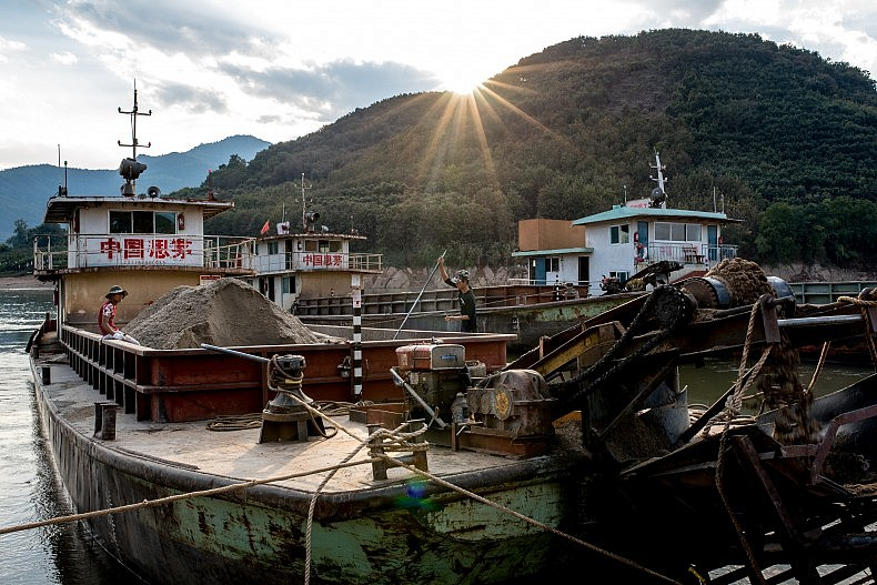 The sun peeks over the mountains at the beginning of another day dredging sand from the Lancang. Photo by Luc Forsyth.