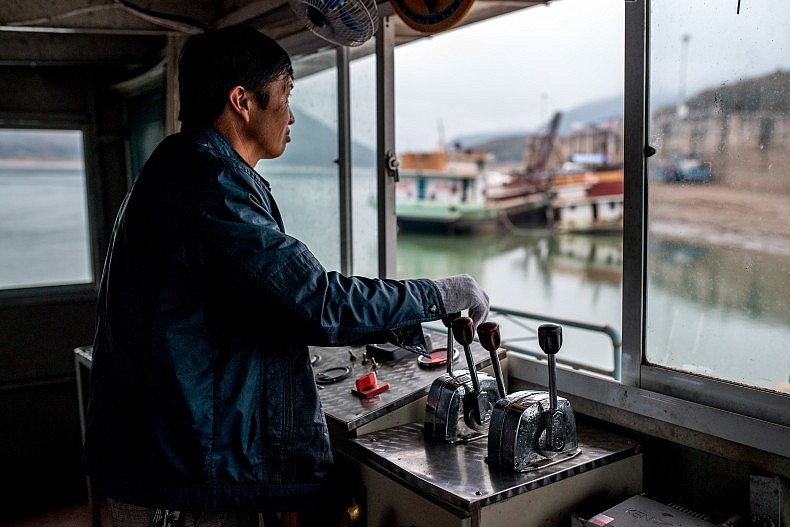 The captain of a sand dredging vessel mans the cockpit in the early morning. Photo by Luc Forsyth.