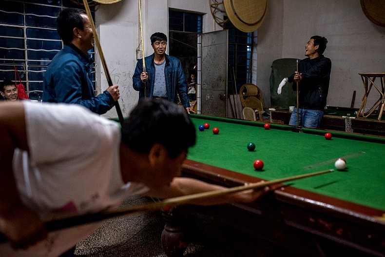The crew of a sand dredging vessel relax by playing pool at the end of their workday. Photo by Luc Forsyth.