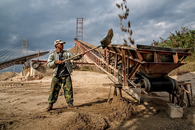 A man shovels spilled sand onto a conveyor belts which moves sand from the dredging boats to the shore for drying. Photo by Luc Forsyth.