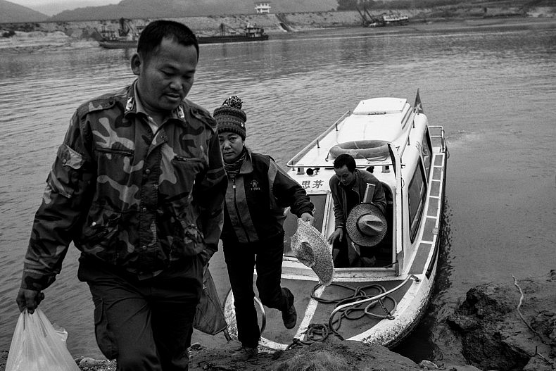 Passengers climb out of  a small ferry that moves between Simaogang and Mengkwang villages in Yunnan, China. Photo by Gareth Bright.