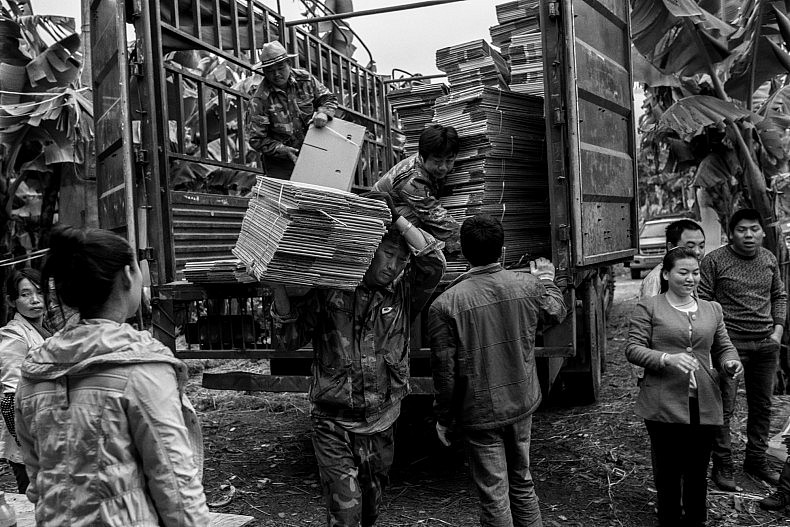 Workers load collapsed cardboard banana boxes on to a truck in Mengkwang village, Yunan, China. They will be assembled and packed at a nearby fruit processing facility. Photo by Gareth Bright.