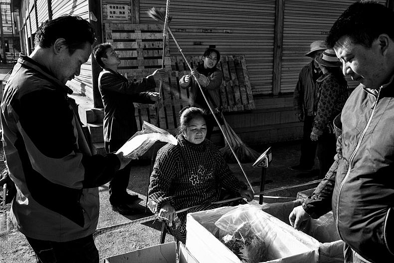 Customers visit a vendor in the Pu'er tea market, Yunan, China. Photo by Gareth Bright.