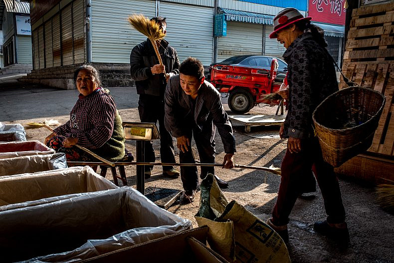 Customers visit a vendor in the Pu'er tea market, Yunan, China. Photo by Luc Forsyth.
