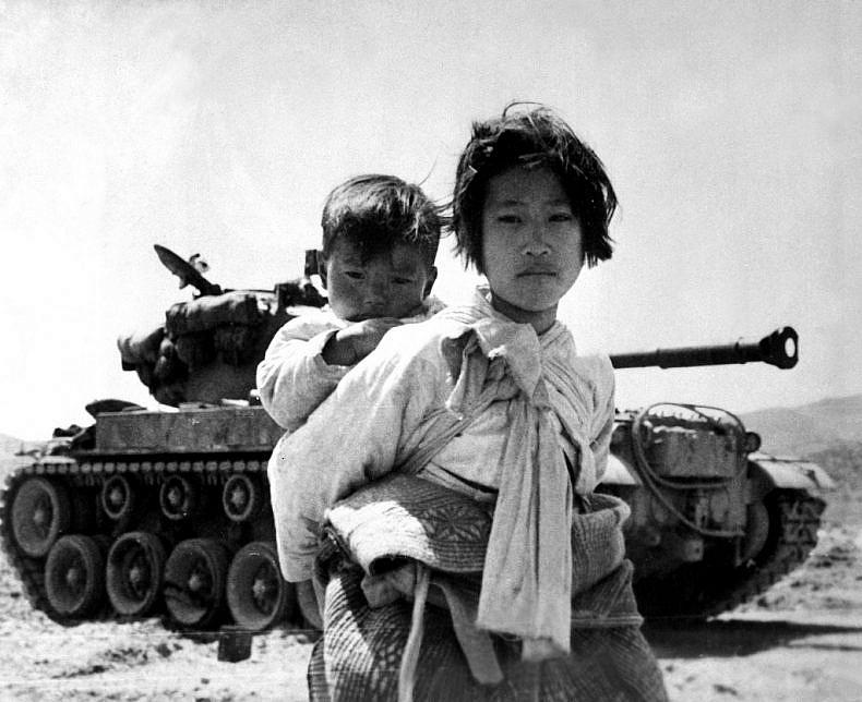 With her brother on her back a war weary Korean girl tiredly trudges by a stalled tank, at Haengju, Korea. June 9, 1951. Maj. R.V. Spencer, UAF. (Navy)