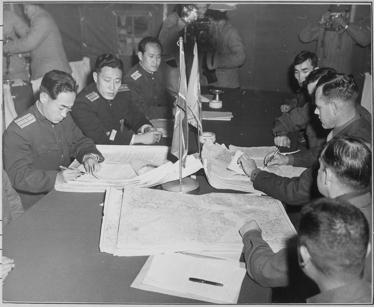 Colonel James Murray, Jr., USMC, and Colonel Chang Chun San, of the North Korean Communist Army, initial maps showing the north and south boundaries of the demarcation zone, during the Panmunjom cease fire talks. General Nam Il is the middle man on the North Korean side. (Navy)