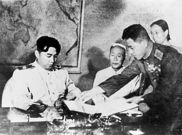 North Korean Premier Kim Il-sung prepares to sign armistice handed to him July 27, 1953, by General Nam Il, head of the communist delegation at Panmunjom. (Eastphoto)