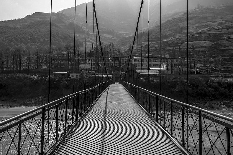 Xialuoga is connected to the outside world only by a steel-cabled suspension bridge. Photo by Gareth Bright.