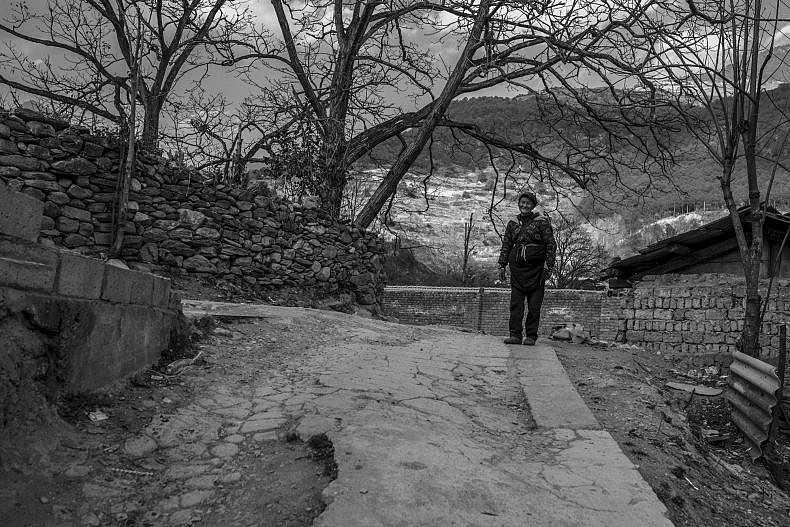 A man stands near his home in Xialuoga. Photo by Gareth Bright.