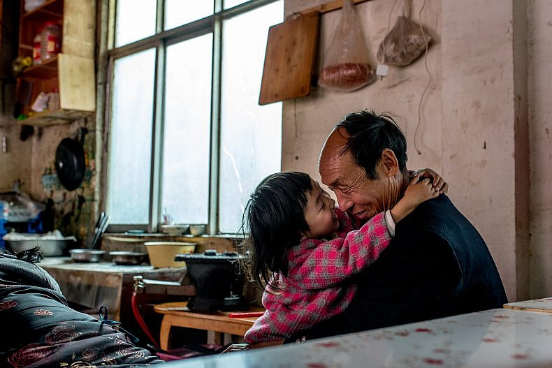 A father plays with his daughter in a small restaurant in the village of Xialuoga. Photo by Luc Forsyth.
