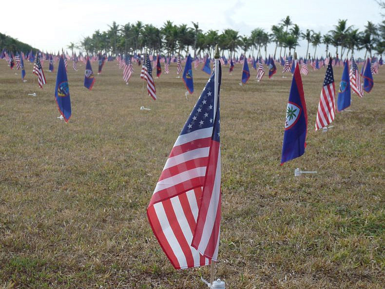 American flags alternate with the flag of Guam in a field. Photo by Jon Letman.