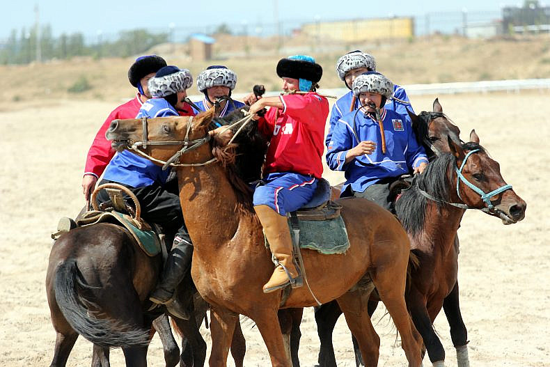 A Russian player (in blue), helps an American (in red) hoiset the heavy goat carcass onto his horse. Photo by Catherine Putz.