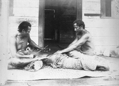 A Samoan tattooist and assistant, carrying out a traditional tatau on a man's back, circa 1895. Photo: Thomas Andrew / Public Domain