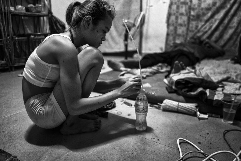 Skinny preparing AK's meth bong, Phnom Penh. Photo by Jonathan van Smit.